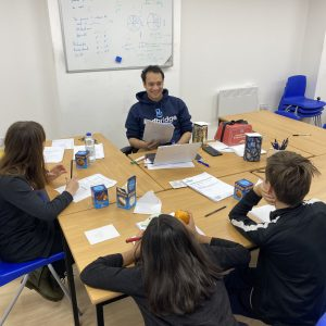 Tutor and students in a tuition centre, pre-Covid, learning together in a group setting whilst having fun and enjoying each other's company