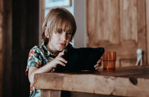 Child using tablet at home to complete online learning activites